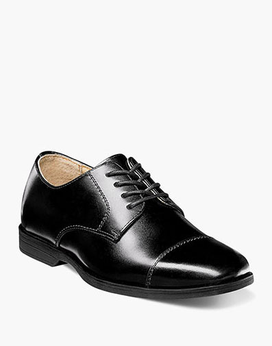 The featured product is the Reveal Jr. Cap Toe Oxford in Black Patent.